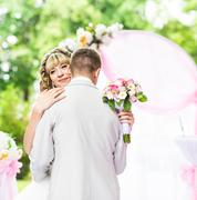 Happy newlywed romantic couple dancing at wedding aisle with pink decorations - stock photo