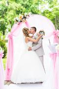 Happy newlywed romantic couple kissing at wedding aisle with pink decorations Stock Photos