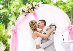 Happy newlywed romantic couple kissing at wedding aisle with pink decorations - stock photo