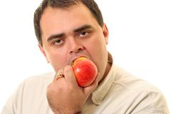 Man bites off an apple - stock photo