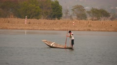 Fisher on boat in waters at Inle lake  in Myanmar with shore background Stock Footage