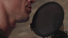 The man read out the text to the microphone in a studio close-up Stock Footage