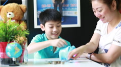 Asian Mother helping son to save money in piggy bank - stock footage