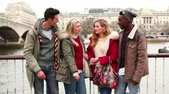 Multiracial group of friends in London looking at a smart phone - stock footage