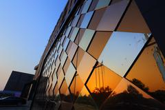Beautiful building with glass wall, reflecting the sky in sunrise Stock Photos