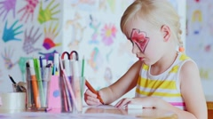 Blonde girl paints in playroom - stock footage