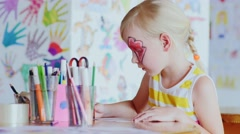 Girl with a festive make-up draws in the games room Stock Footage