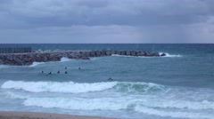 Surfers wait for good wave, stand on severe sea, strong cool breeze, rainy Stock Footage