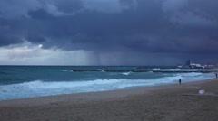 Surfer run along empty beach, severe weather, leaden sky, rainy clouds - stock footage
