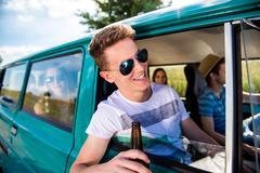 Teenagers inside an old campervan, drinking beer, roadtrip Kuvituskuvat
