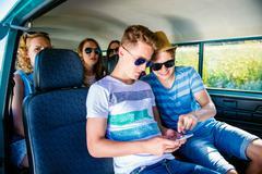 Teenagers with smartphone inside an old campervan, roadtrip Kuvituskuvat