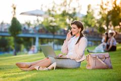 Businesswoman sitting in park checking her smartphone, sunny sum - stock photo