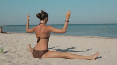 Young Girl is Making Workout While the Practice of Yoga on the Beach in a Warm Stock Footage