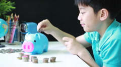 Little asian boy saving money in to piggy bank - stock footage