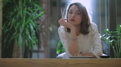 Girl sitting in thought and licking chopsticks - stock footage