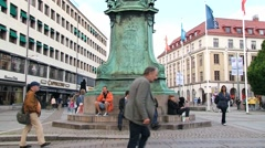 People relax next to the statue of King Karl IX in Gothenburg, Sweden. Stock Footage