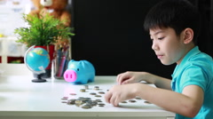 Happy Asian boy counting coins from piggy bank and put together Stock Footage