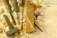 Carpenter tools on wooden table with sawdust. Craftperson workplace top view Stock Photos