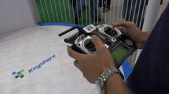 Chinese drone company employee using remote controller at trade show Stock Footage
