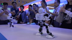 Chinese people take photos of dancing humanoid robots at technology trade show Stock Footage