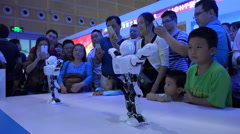 China robotics industry, technology exhibition, dancing robots, amused crowds Stock Footage