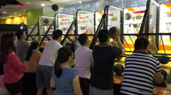 Chinese families play basketball in a gaming arcade in Shenzhen, China Stock Footage