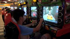Chinese teenagers play racing video games in an arcade in Shenzhen Arkistovideo