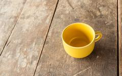 Stock Photo of Yellow coffee cup on old wooden table