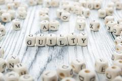 guilty word written on wood block. Wooden Abc - stock photo
