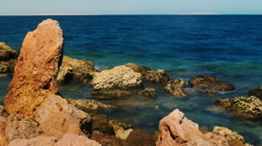 Surf at the rocks - Red stone on a background of blue sea Stock Footage
