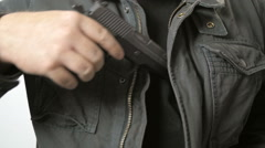 Man Pulls Handgun out of Coat in Slow Motion Stock Footage