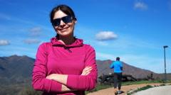 Portrait of happy sporty woman in country, man jogging on sidewalk Stock Footage