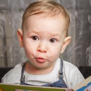 Child repeats sounds from audio book Stock Photos