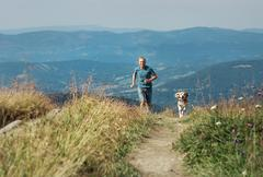 Man runs with his dog on the green meadow in mountain Kuvituskuvat