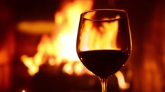 Stock Video Footage of Red Wine Glass and a Fireplace Background