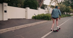 Teen hipster girl skateboarding on a suburban road Stock Footage