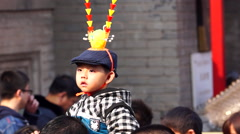 Boy wearing the crown of monkey king on his father's shoulder in a temple fair Stock Footage