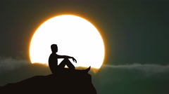 The man sit on the edge of a cliff on the background of sunrise. Real time - stock footage