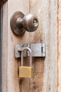 Rusty old door knob and padlocks - stock photo