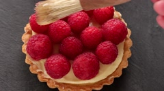 Unfinished to eat tartlet with custard and fresh ripe raspberries and brush for Stock Footage