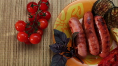 Grilled sausages and vegetables lying on the plate Stock Footage