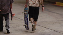 Rear view of two skateboarders walking on the street with skateboard - stock footage