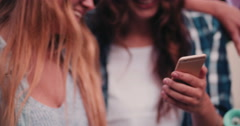 Teen girl friends in hipster wear smiling at smart phone Stock Footage