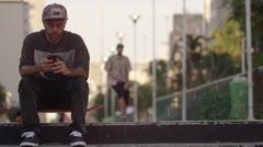 Two skateboarders sitting together and looking at phone on the steps - stock footage