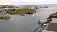 Boat navigates by the harbor of the picturesque town of Smogen, Sweden. Stock Footage