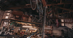 Bicycle hanging by rope from rafters in a garage Stock Footage