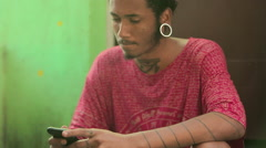 Funky young man typing a message on his mobile phone Stock Footage