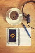Play button on smart phone with headset, notebook, pencil, coffee cup on wood - stock photo