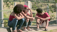 Young funky friends sitting near a fence and chatting Stock Footage