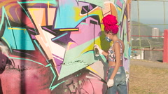Two young women painting graffiti on wall - stock footage
